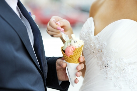 bride with an ice-cream which is in the hand of the groom Imagens