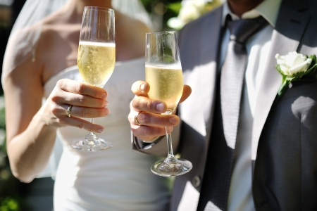 Bride and groom making a toast with champagne glasses after wedding ceremony Imagens