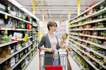 mulher bonita com um carrinho de compras e escolhendo mercadorias no supermercado