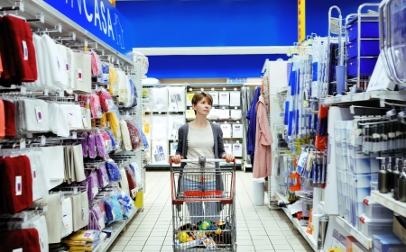 pretty smiling woman pushing cart looking at household items in supermarket