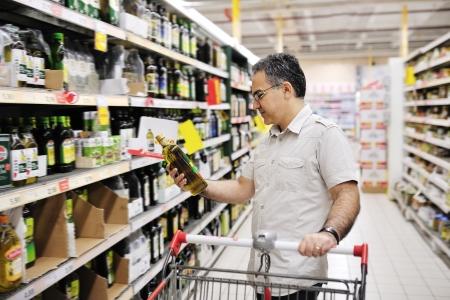 oleos: hombre con la cesta de compras y mirar la comida en el supermercado Foto de archivo