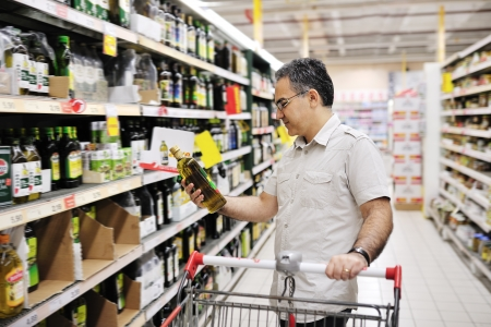 man with cart shopping and looking at food in supermarket