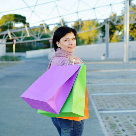 colored paper: smiling woman with a lot of colored paper shopping bags Stock Photo