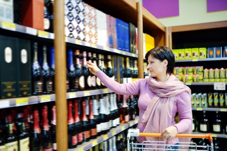 resale: pretty caucasian woman shopping and choosing goods at supermarket