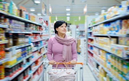 resale: pretty smiling woman pushing shopping cart looking at goods in supermarket