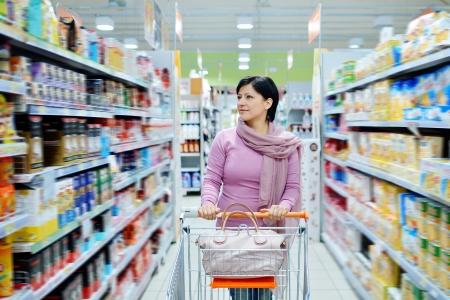 꽤 웃는 여자가 슈퍼마켓에서 상품을 찾고 쇼핑 카트를 밀고 스톡 콘텐츠