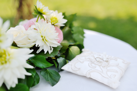 wedding rings on a little white pillow near flowers