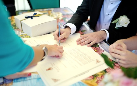 Groom signs documents at a wedding ceremony photo
