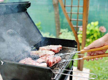 grill tongs sausage: Man in skirt at a barbecue grill, preparing the meat for a garden party  Stock Photo