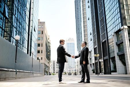 contrato de trabajo: dos hombres de negocios d�ndose la mano en el fondo moderno de oficinas edificios corporativos