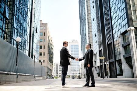 two businessmen shaking hands on background modern office corporate buildings photo