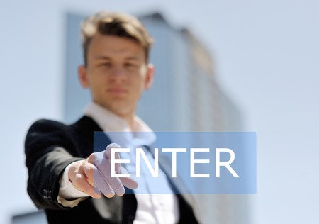 man pushing virtual enter button on business building background - technology, internet and networking concept photo
