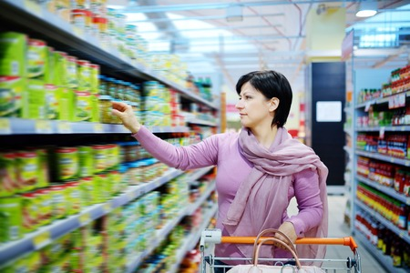 resale: pretty woman with shopping cart choosing at goods in supermarket Stock Photo