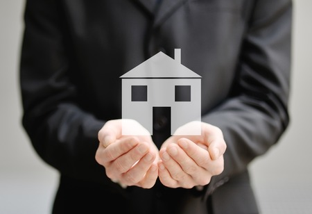 protection hands: the hands of a man holding a house - insurance, security and protection concept Stock Photo