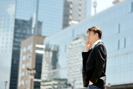 corporate building: smiling young businessman talking on cell phone on background modern office corporate buildings Stock Photo