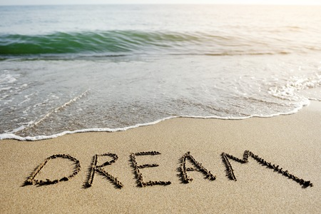 dream word written on the sand of the beach - positive thinking concept photo