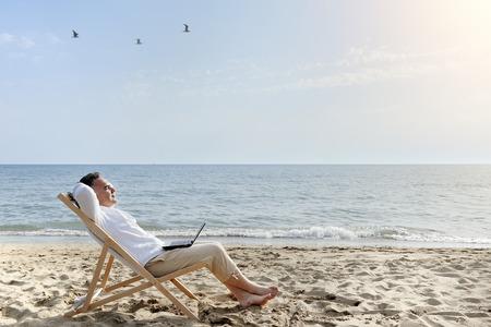 man met laptop ontspannen op het strand zitten op de ligstoel Stockfoto