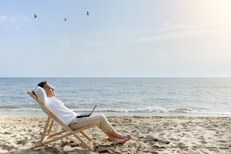 man with laptop relaxing on the beach sitting on deck chair