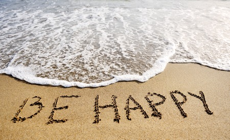 good mood: be happy words written on the sand of the beach - positive thinking concept