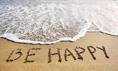 seien Sie fröhliche Worte, die auf den Sand des Strandes geschrieben werden - positives Denkkonzept Standard-Bild