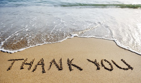 agradecimiento: gracias las palabras escritas en la arena de la playa Foto de archivo