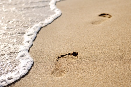 footprints on the sand of the beach at dawn photo