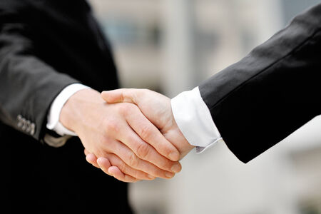 two businessmen shaking hands - business deal partnership concept photo