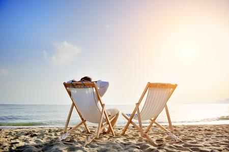 man op het strand ontspannen op de ligstoel te wachten op zijn vriendin