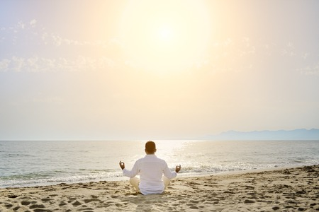 man doing yoga meditation exercises on the beach at sunset- healthy lifestyle concept Imagens