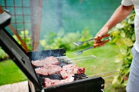 barbecue party: Man at a barbecue grill preparing meat for a garden party Stock Photo