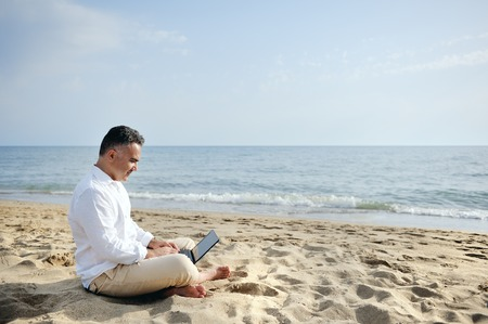relaxed man with laptop working on the beach sitting on the sand