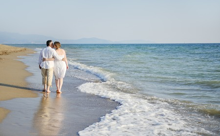 tenderly: romantic couple tenderly embracing walking together on the beach Stock Photo