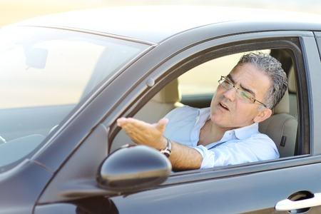 road rage:  irritated male driving his car in traffic - road rage concept