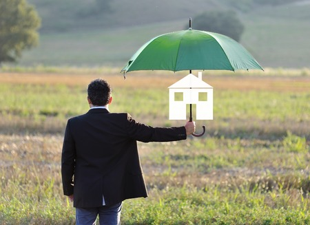 home insurance protection concept, businessman with umbrella in the field