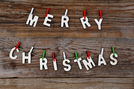 Merry Christmas greeting message on wooden background Imagens