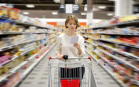retail stores: caucasian woman with shopping list in hand pushing cart looking at goods in supermarket