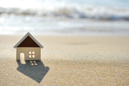 real estate sign: little house on the sand beach near sea Stock Photo