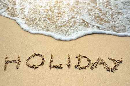 holiday written on the sand beach near sea photo