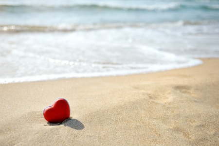 red heart on sandy sea beach - love relax concept