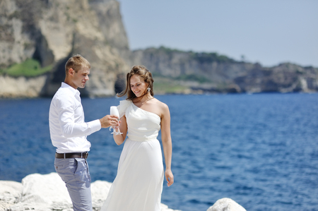 young bride and groom making a toast with champagne near sea, Naples, Italy photo