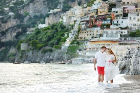 positano: smiling happy young couple walking on the beach of Positano