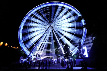 ferris wheel in motion at amusement park at night