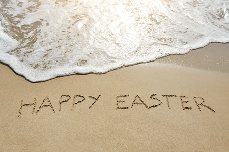 happy easter written on sand near sea