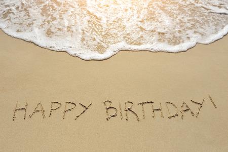 felicitaciones cumplea�os: feliz cumplea�os escrito en la arena de la playa Foto de archivo