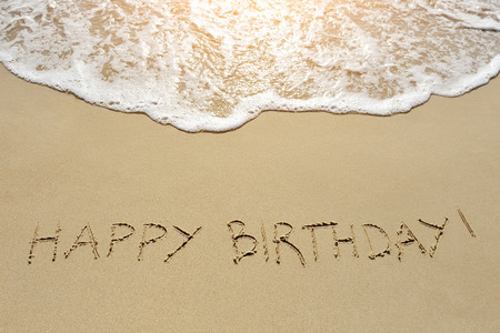 happy birthday written on the sand beach Banco de Imagens