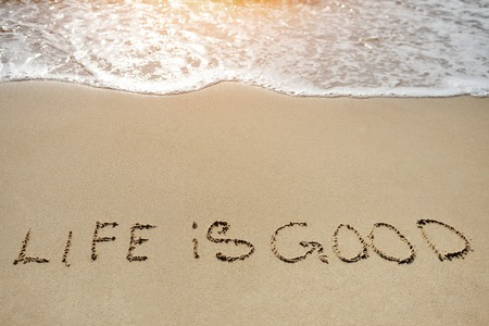 life in good written on the sand beach - positive thinking concept