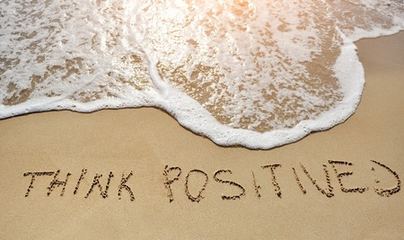 positive thinking: think positive written on the sand beach - positive thinking concept