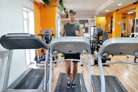 young handsome athlete running on tapis roulant in the gym - fitness wellness healthy lifestyle concept