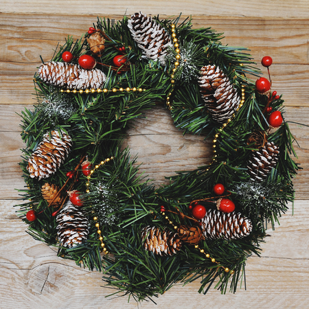good wishes: christmas decoration with pinecones on wooden background