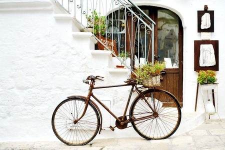 vintage rusty bicycle against a wall in white city Ostuni, Apulia, Italy. - artistic picture italian style concept